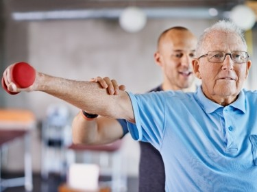 Physiotherapist helping a senior man with weights