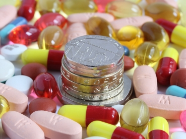 British money surrounded by pills, tablets and capsules