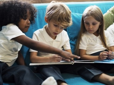 Elementary school children reading a book, photo by Rawpixel.com/Adobe Stock