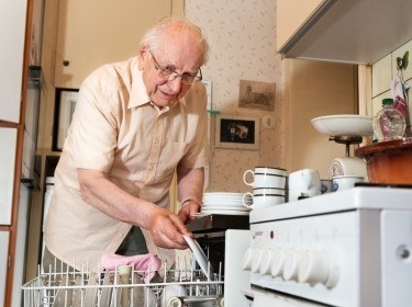 Elderly man unloading the dishwasher
