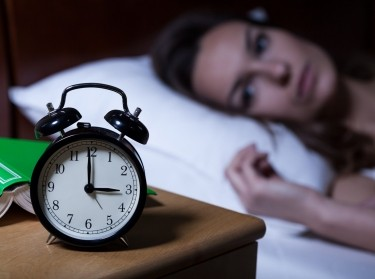 Woman with insomnia, and alarm clock on night table showing 3 a.m.