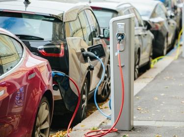 Electric vehicle at charging station, photo by scharfsinn86 J&K/Adobe Stock