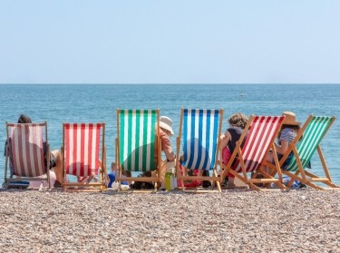 Rear view of group seated in striped deckchairs at the seaside on a sunny summer day, photo by Ian/Adobe Stock