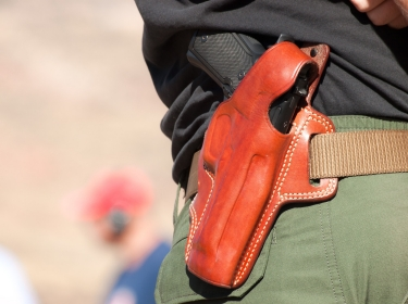 A person wearing a gun in a holster