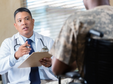 Doctor talks with armed forces veteran during a health evaluation