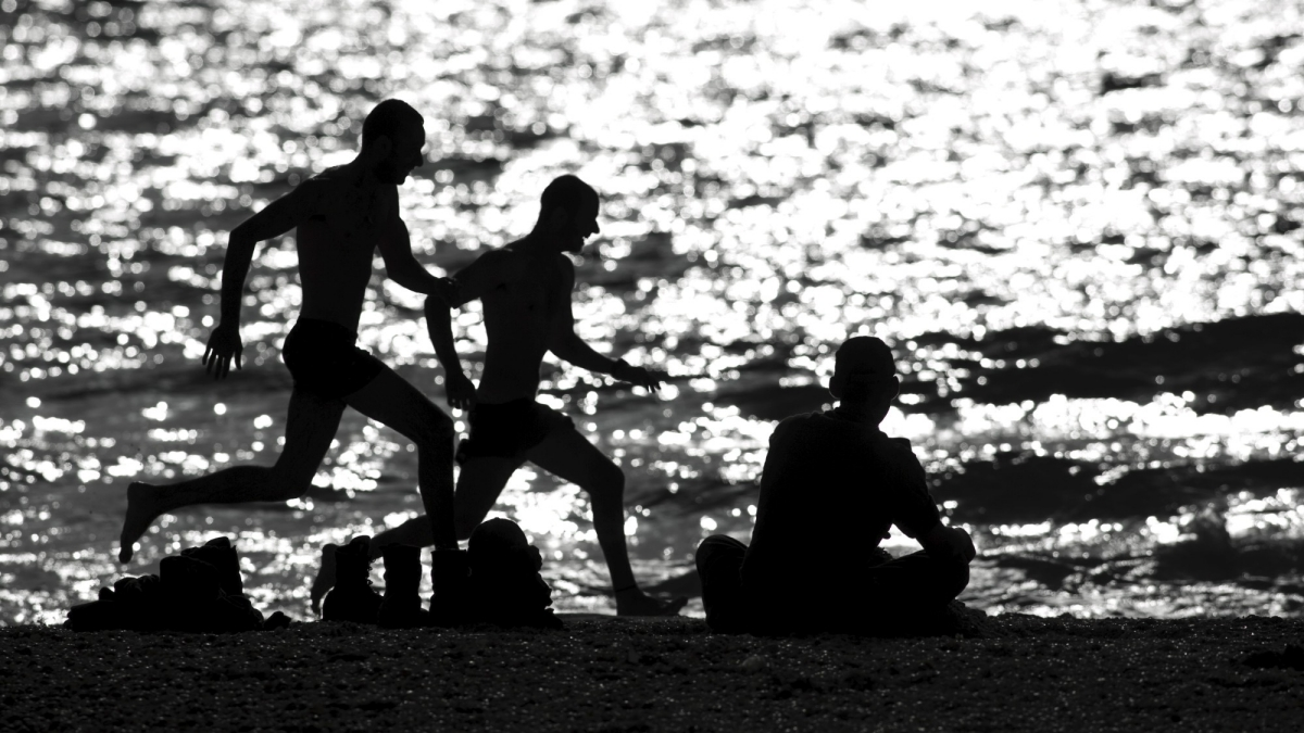 Off-duty Israeli soldiers run on the shore of the Mediterranean sea.