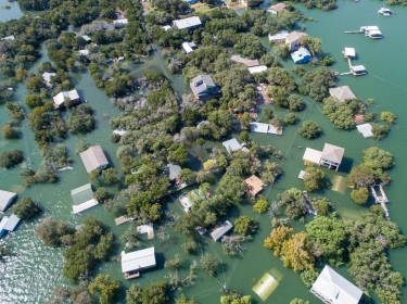 An aerial view of Central Texas homes under water at Graveyard Point neighborhood community in the flood plain of Lake Travis, photo by RoschetzkyIstockPhoto / Getty Images