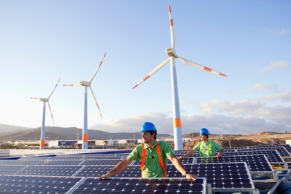Two workers wearing hard hats on a solar farm with wind turbines in the background
