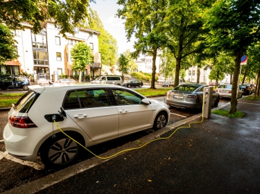 An electric car plugged into a charging station while parked on a residential street.