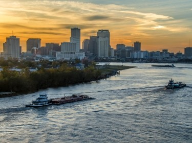 Barges traveling up the Mississippi River towards New Orleans, Louisiana, with the city skyline in the background.