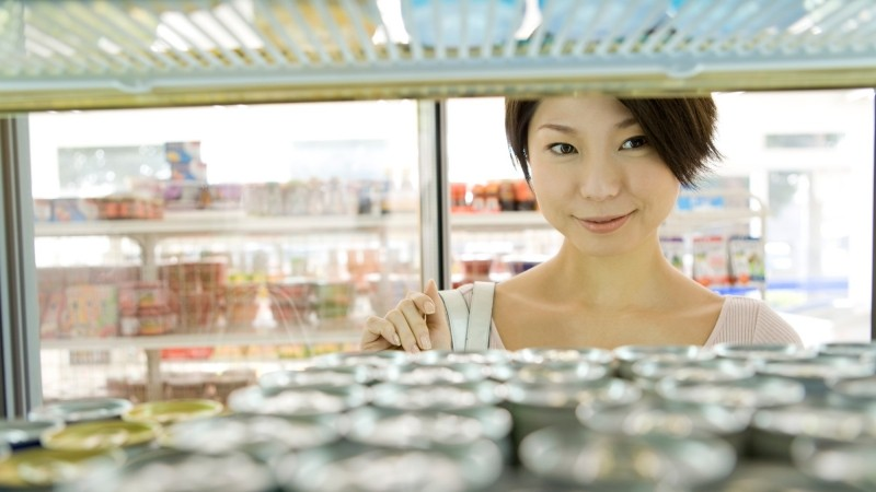 A woman shops at a convenience store as seen from inside a beverage cooler