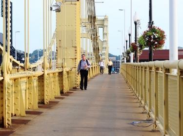 Pedestrians walk across the Roberto Clemente Bridge in Pittsburgh