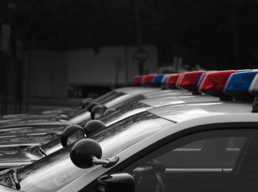 A fleet of black and white police cars with the red, white, and blue lights atop. Photo by