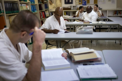 Offenders read books and write papers at a library in the Texas Department of Criminal Justice men's prison in Rosharon, Texas
