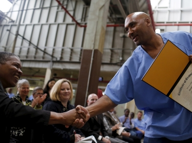 Jerome Boone shakes hands with members of the audience after graduating from a computer coding program at San Quentin State Prison in California, April 20, 2015