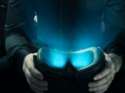Hands holding virtual reality goggles with light glowing from inside, photo by  Daniel Krasoń / Adobe Stock