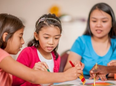 A group of elementary school students work on a painting together