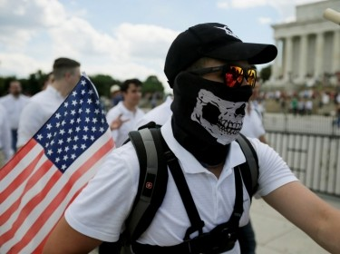 """masked demonstrator carrying a U.S. flag leaves the Lincoln Memorial after self proclaimed """"White Nationalists"""", white supremacists and members of the """"alt-right"""" gathered for what they called a """"Freedom of Speech"""" rally at the memorial in Washington, June 25, 2017, photo by Jim Bourg/Reuters"""