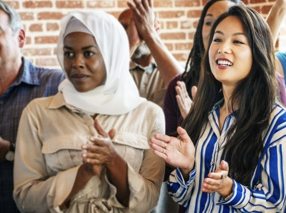 A group of people of diverse racial backgrounds stand clapping. Photo by rawpixel.com / Adobe Stock
