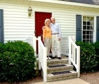 Elderly couple in front of their house