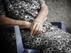 The crossed hands of an elderly woman.