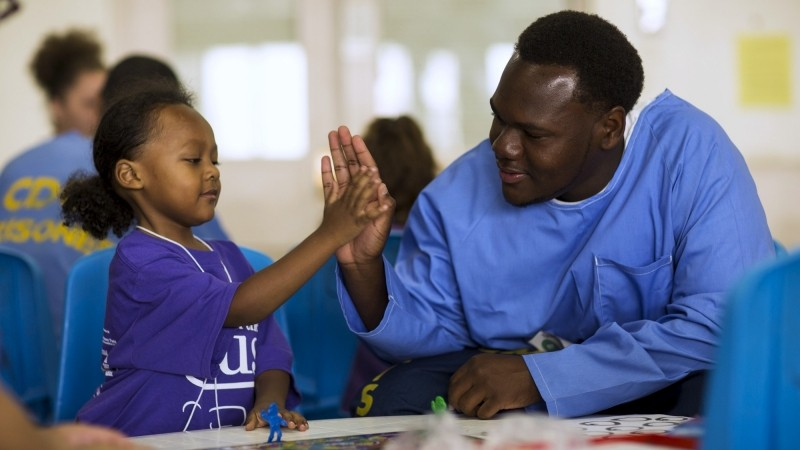 """Inmate Tyrone Parker high-fives his son Tyrone Parker Jr. during a special Father's Day visit part of the """"Get On The Bus"""" program at California Men's Colony in San Luis Obispo, California May 30, 2015, photo by Mario Anzuoni/Reuters"""