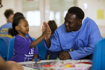 "Inmate Tyrone Parker high-fives his son Tyrone Parker Jr. during a special Father's Day visit part of the ""Get On The Bus"" program at California Men's Colony in San Luis Obispo, California May 30, 2015, photo by Mario Anzuoni/Reuters"