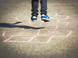 Close up of little boy jumping on a chalk hopscotch outline
