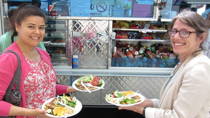 Women holding food in front of a Loncheras truck