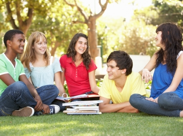 group of teenagers laughing in a park