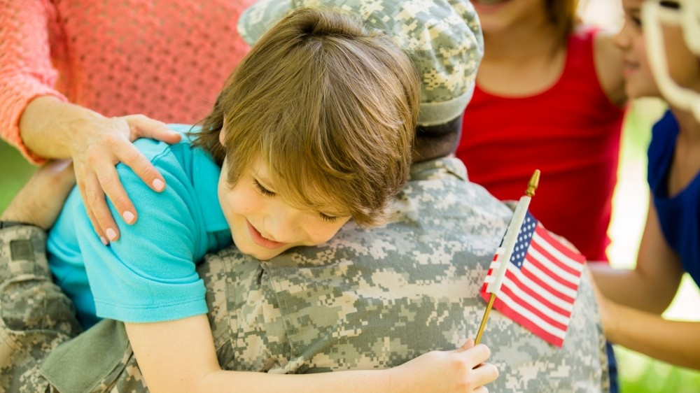 U.S. military veteran welcomed home by his family and hugging his son