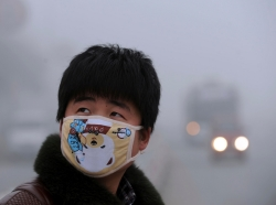 A man wearing a mask looks up as he walks on a street on a foggy day in Bozhou, China.